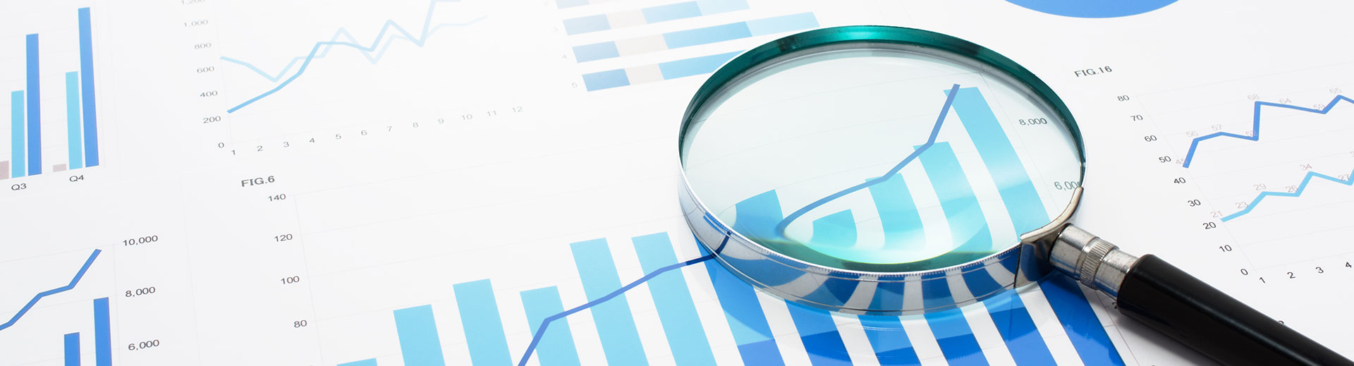 Photo of magnifying glass over financial reports