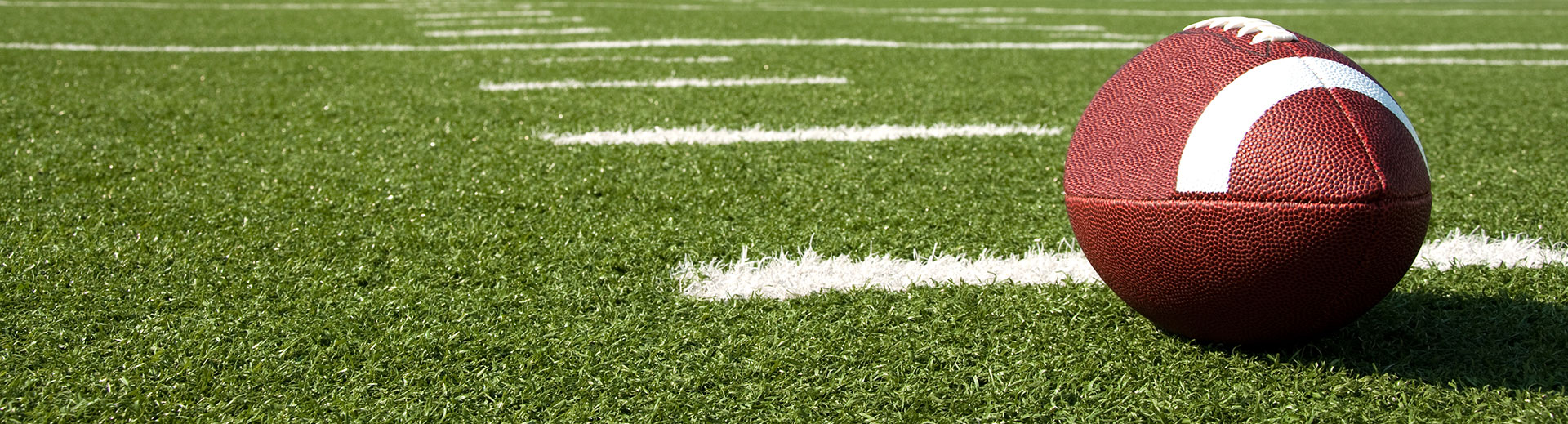Photo of a football resting on a football field